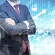 Analyst with crossed hands is standing in front of the digital financial calculations and predictions on the background. A concept of the capital market transactions and forex deals. — Stock Photo #75243637