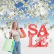 A happy young woman with the colourful shopping bags from the fancy shops. Dollar notes are falling down from the sky as a concept of the sale and discount. Concrete background. — Stock Photo #75243715