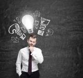 Young manager ponders about new business ideas. A light bulb as a concept of new ideas. — Stock Photo