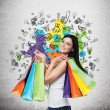 Beautiful smiling young woman with the colourful shopping bags from the fancy shops. Concrete background with drawn shopping icons. — Stock Photo #75841559