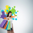 Beautiful smiling young woman with the colourful shopping bags from the fancy shops. Studio background with drawn shopping colorful spots. — Stock Photo #75841569