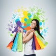 Beautiful smiling young woman with the colourful shopping bags from the fancy shops. Studio background with drawn shopping colorful spots. — Stock Photo #75841597