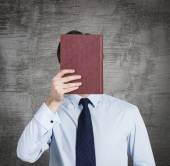 A person holds a red book in front of the head. Concrete background. — Stock fotografie