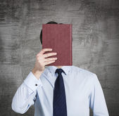 A person holds a red book in front of the head. Concrete background. — Fotografia Stock