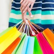 A lady in a skirt is holding a lot of colourful shopping bags. — Stock Photo #77134215