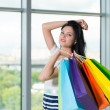 Beautiful smiling brunette woman with the colourful shopping bags from the fancy shops. Panoramic view in blur on the background. — Stock Photo #77134355