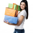 A brunette woman is holding three colourful gift boxes. Isolated. — Stock Photo #77134503