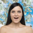 Portrait of an astonished brunette girl. Dollar notes are falling down over the sky background. — Stock Photo #77134561