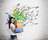 A brunette woman is holding three colourful gift boxes. Drawn sketch on the wall with arrows and shopping icons. Concrete background. — Stock Photo