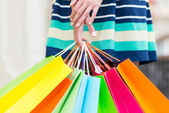 A lady in a skirt is holding a lot of colourful shopping bags. — Stock Photo