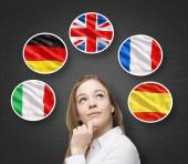 Beautiful lady is surrounded by bubbles with european countries' flags (Italian, German, Great Britain, French, Spanish). Learning of foreign languages concept. Blackboard background. — Stock Photo