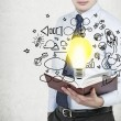 Young businessman is holding a book with flying around business icons and a light bulb as a concept of the new business ideas. — Stock Photo #77215465
