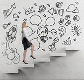 Young business woman is going up to the stairs. A concept of a brainstorm. Business icons are drawn on the wall. Concrete background. — Stock Photo