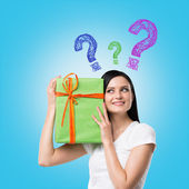 A brunette woman is holding a green gift box and question mark as a concept of gift uncertainty. Blue background . — Stockfoto