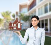Beautiful brunette property agent presents a new house for sale. Luxury villa in blur as a background. — Stock Photo