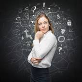 A portrait of a beautiful lady with questioning expression who is looking the best solution for the business problem. Chalk Business icons are drawn over the black chalkboard. — Stock Photo