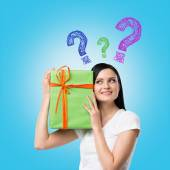 A brunette woman is holding a green gift box and question mark as a concept of gift uncertainty. Blue background . — Stock Photo