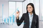 Beautiful woman drawing on a glass board a growing bar chart. Panoramic corner office on background. — Stock Photo