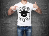 Close-up of a man pointing his finger to the chest with the sketch of the graduation hat. A concept of the MBA degree. shooting mark. Black chalk board on background. — Stock Photo