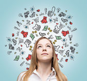 Beautiful lady is thinking about shopping. Colourful shopping icons are flying in the air. — Stock Photo