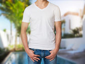 Young man in a white V shape t-shirt, hands in pockets. Villa with swimming pool in blur on the background. — Stock Photo