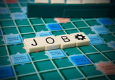 The word 'JOB' is made of the scrabble tiles. Scrabble game board as a background. — Stock Photo