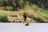Young Malagasy rafter man rowing traditional canoe on river, Mad — Photo