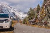 Car parked road mountains snow autumn — Stock fotografie