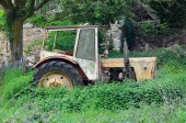Old tractor in the abandoned garden — Stock Photo