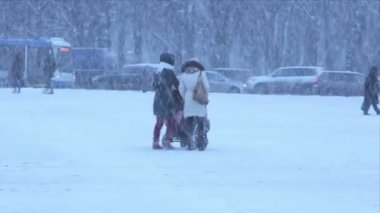 Two women with a children's carriage during a heavy snowfall in the winter — Vídeo de stock