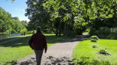 Man walks through the park on a sunny day — Stock Video