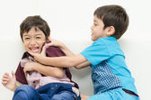 Little sibling boy fighting on sofa — Stock Photo