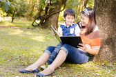 Mother and son read a book together in the park — Stock Photo