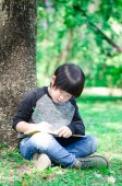 Little asian boy writing book in the park — Stock Photo