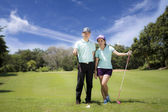 Young sportive couple playing golf on a golf course — Stock Photo