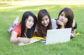 College student lying down on the grass working on laptop — Stock Photo