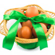 Basket with eggs and green ribbon isolated on white background — Stock Photo #65002469