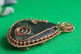 Pendent from the stone braided by a copper wire close up — ストック写真