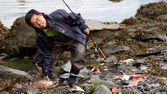 Asian fisherman caught salmon in Seward — Stock Photo