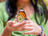 Common Tiger Butterfly hanging on girl is finger — Stock Photo