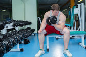Man makes exercises with dumbbells. — Stock Photo