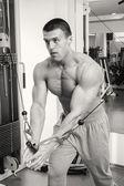 Man makes exercises at  gym — Stock Photo