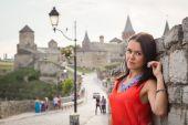 Brunette girl against old castle wall — Stock Photo