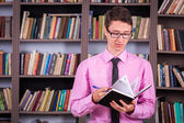 Student holding book at library — Stock Photo