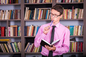 Student holding book at library — Foto de Stock