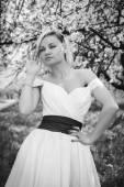 Blonde in white dress in spring garden — Stock fotografie