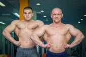 Two bodybuilders demonstrating muscles — Stock Photo