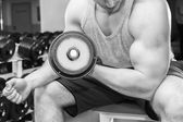 Man with muscular arms holding a dumbbell — Fotografia Stock
