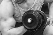 Man holding dumbbell in suspense — Stock Photo