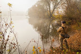 Fisherman with spinning on river bank — Stock Photo